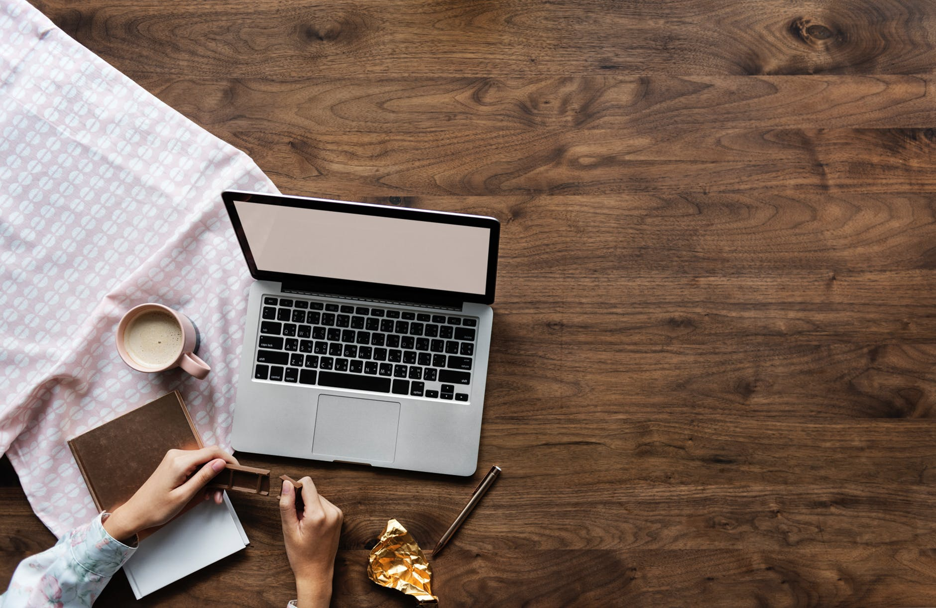 person holding chocolate bar near laptop